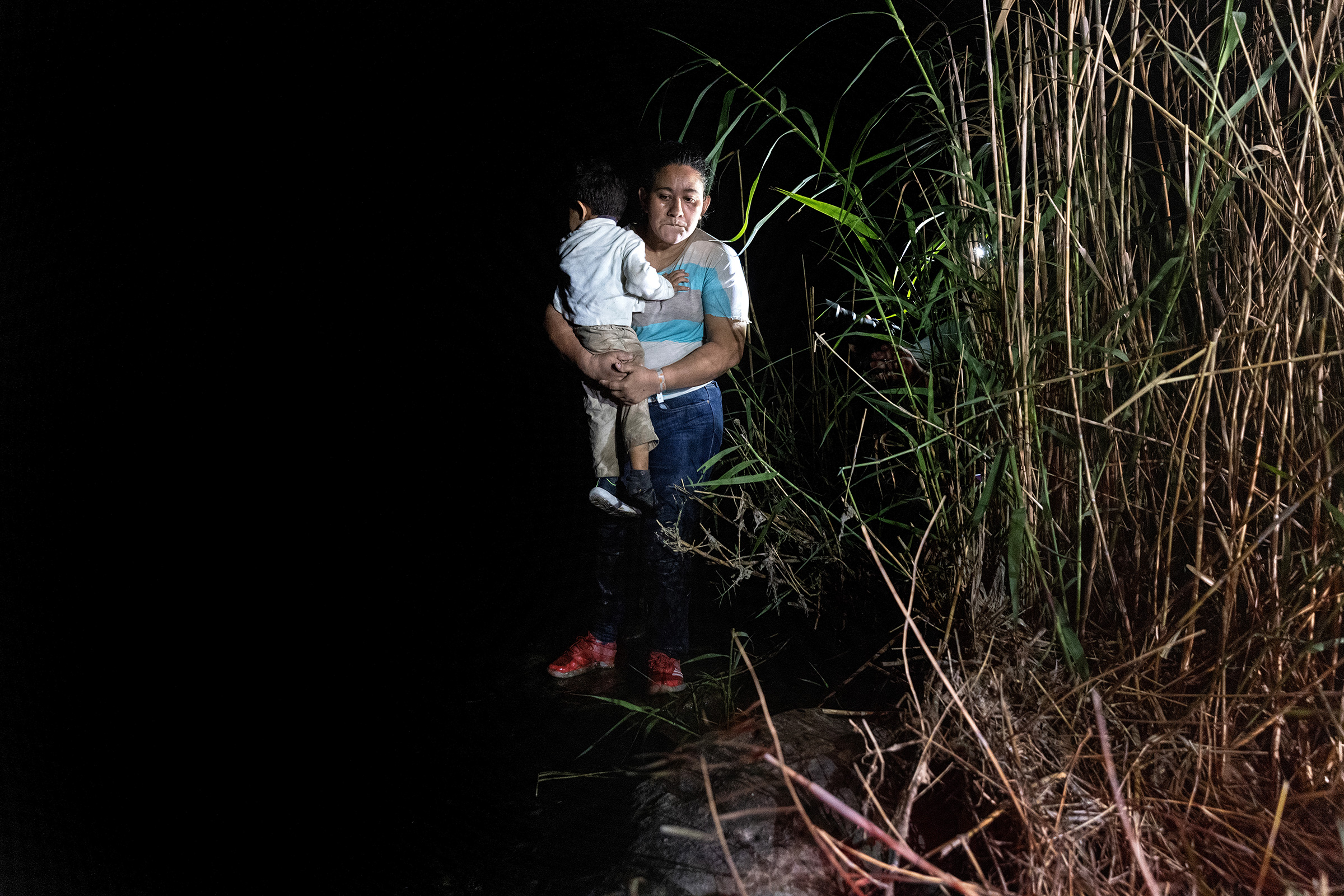 A mother holds her son on the bank of the Rio Grande in Roma, Texas, after being smuggled across the U.S.-Mexico border on April 14, 2021.