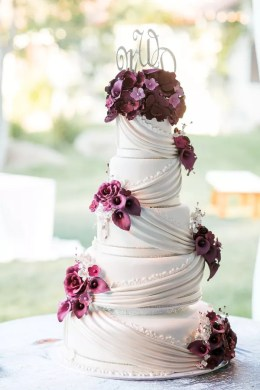 Purple Wedding Cakes Classic Ivory Cake with Draping and Dramatic Purple Flowers