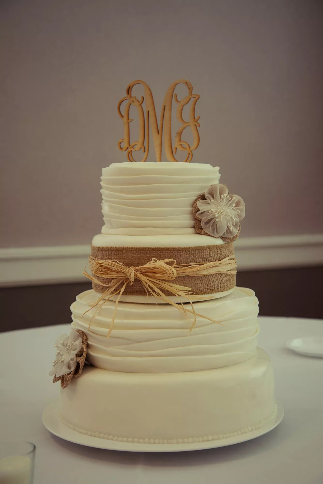 Rustic Wedding Cake With Burlap And Straw Ribbon And Monogram Cake Topper