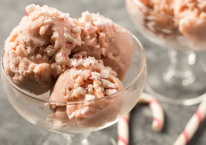 Two glass dessert dishes with peppermint ice cream, with two candy canes sitting next to them