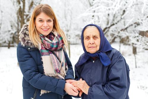 Junge und alte Frau halten sich die Hände