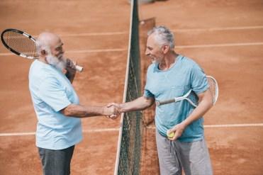 Zwei Männer geben sich die Hand beim Tennisspiel. rheumatische Beschwerden