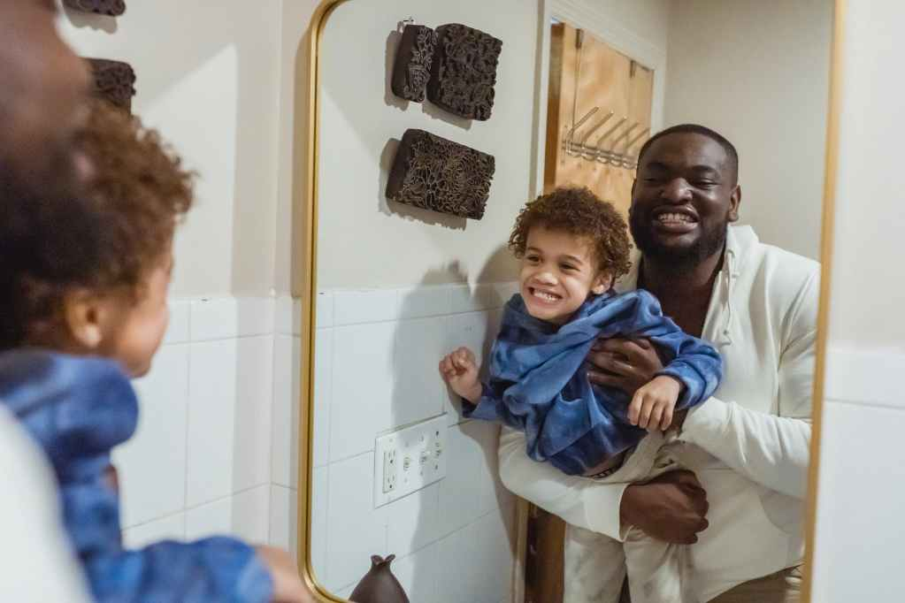 positive black father and son in bathroom