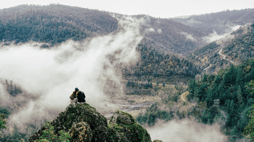 A couple looks out a vast mountain range
