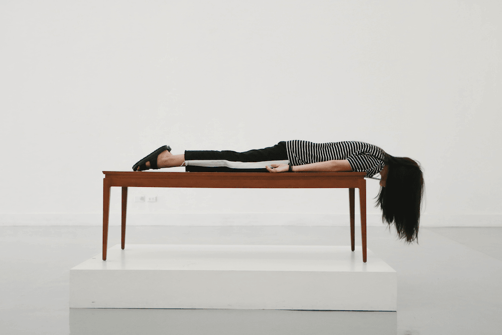 A woman lies face down on a table with her head hanging off the end