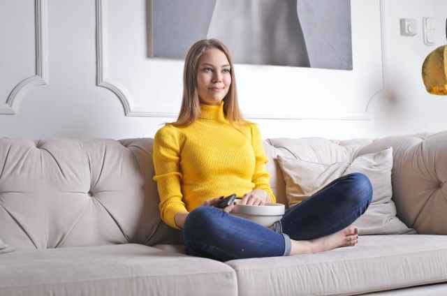 cheerful woman watching tv at home