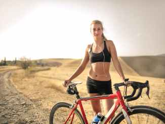 confident athletic woman with bicycle on countryside road