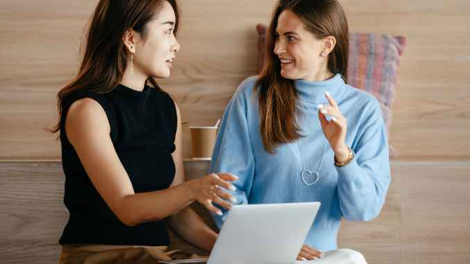 multiracial businesswomen with laptop talking about work