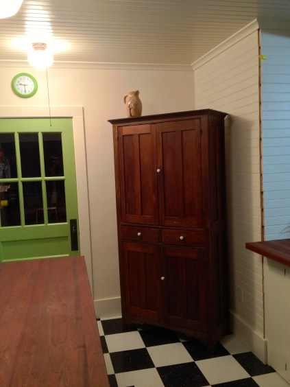 Antique Oak Cupboard on black and white tile floor