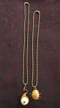 Eyeball and beetle necklaces