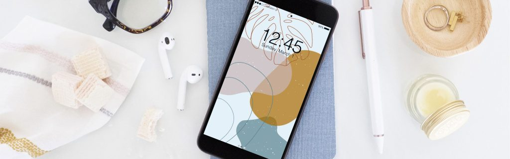 A new, modern, design for your phone background this March. The pattern has muted pink, yellow, and blue oblong circles and a floral print at the top of the screen.
