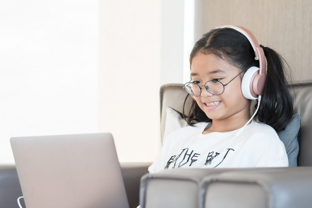 Digital technology education concept of school kid lifestyle with headphone using internet learning and reading e-book on mobile computer software for educational studying and playing online game