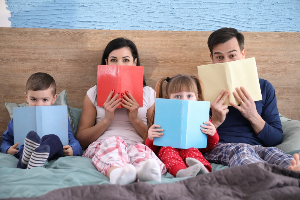 Happy family reading books in bed