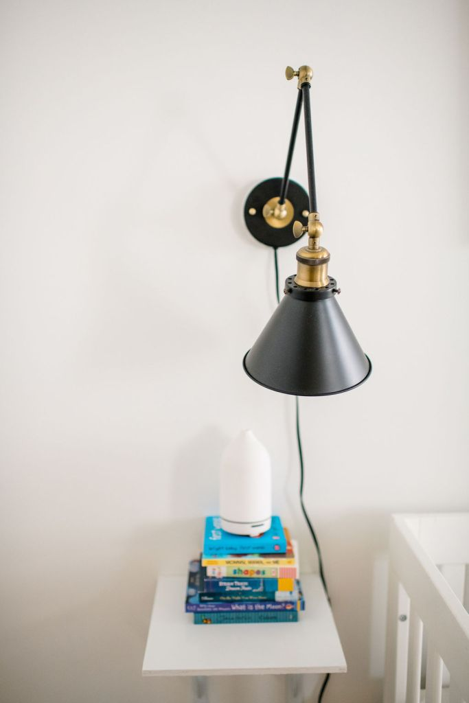 A black wall sconce in a nursery for infants. Also a stack of books with an essential oil diffuser on top.