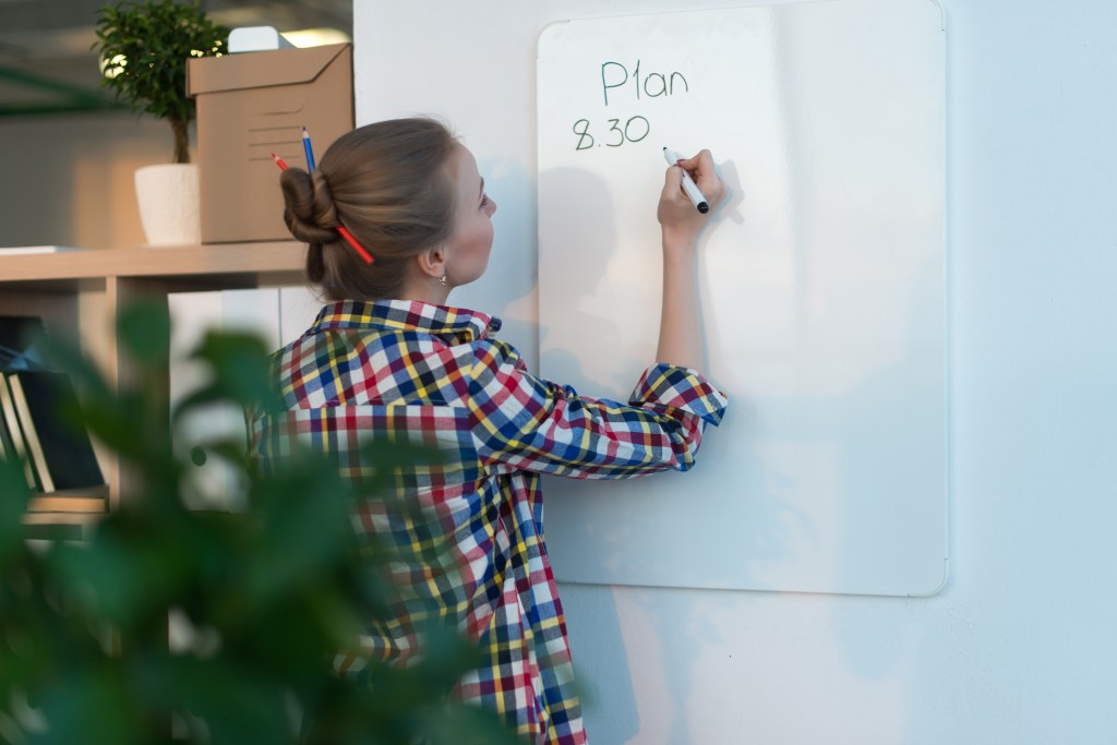 Young woman writing day plan on white board, holding marker in right hand. Student planning schedule rear view portrait