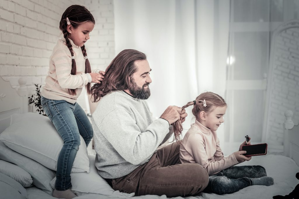 Family of father and two daughters braiding each others hair siting on bed of a happy day