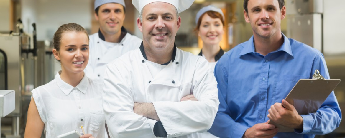 Head chef posing with the team behind him