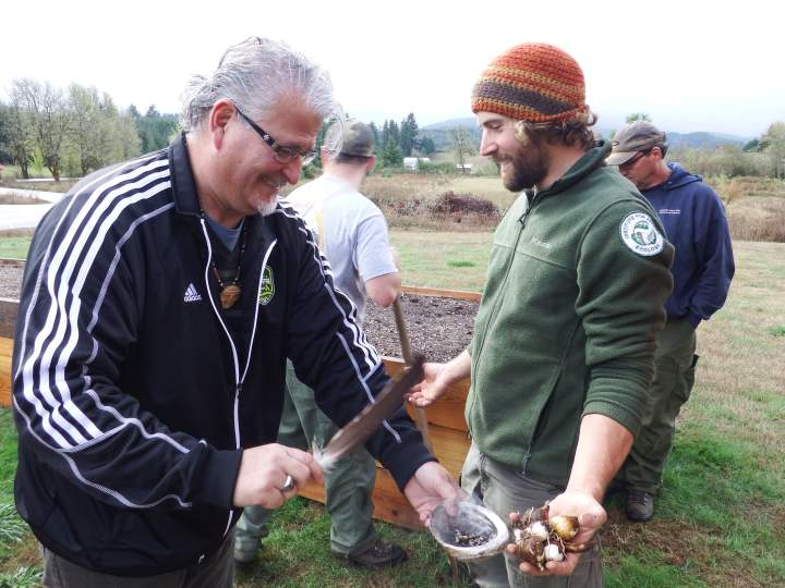 Tribal Council member Jon George blessing camas before planting at the raised beds at Grand Ronde
