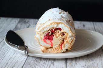 white chocolate and raspberry meringue roulade on a plate