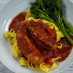 Slow cooker Sausage Casserole in a white bowl with fresh pasta and broccoli