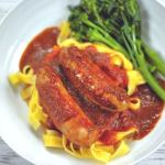 slow cooker sausage casserole and green vegetables served on fresh egg pasta