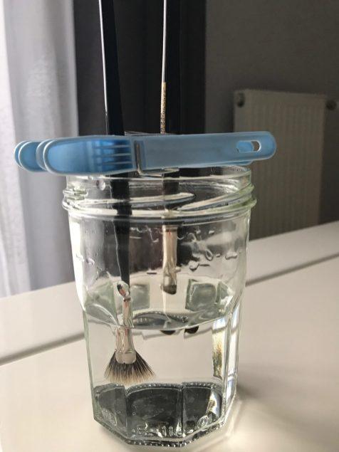 Utiliser un pot à confiture avec des pinces à linge pour maintenir la tête des pinceaux dans l'eau