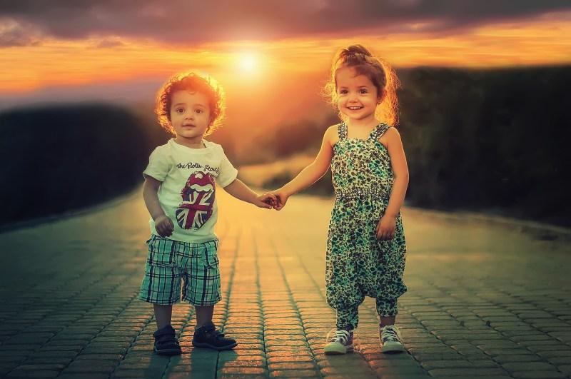 Deux enfants marchent main dans la main sur fond de coucher de soleil et ont confiance l'un dans l'autre et dans l'avenir.