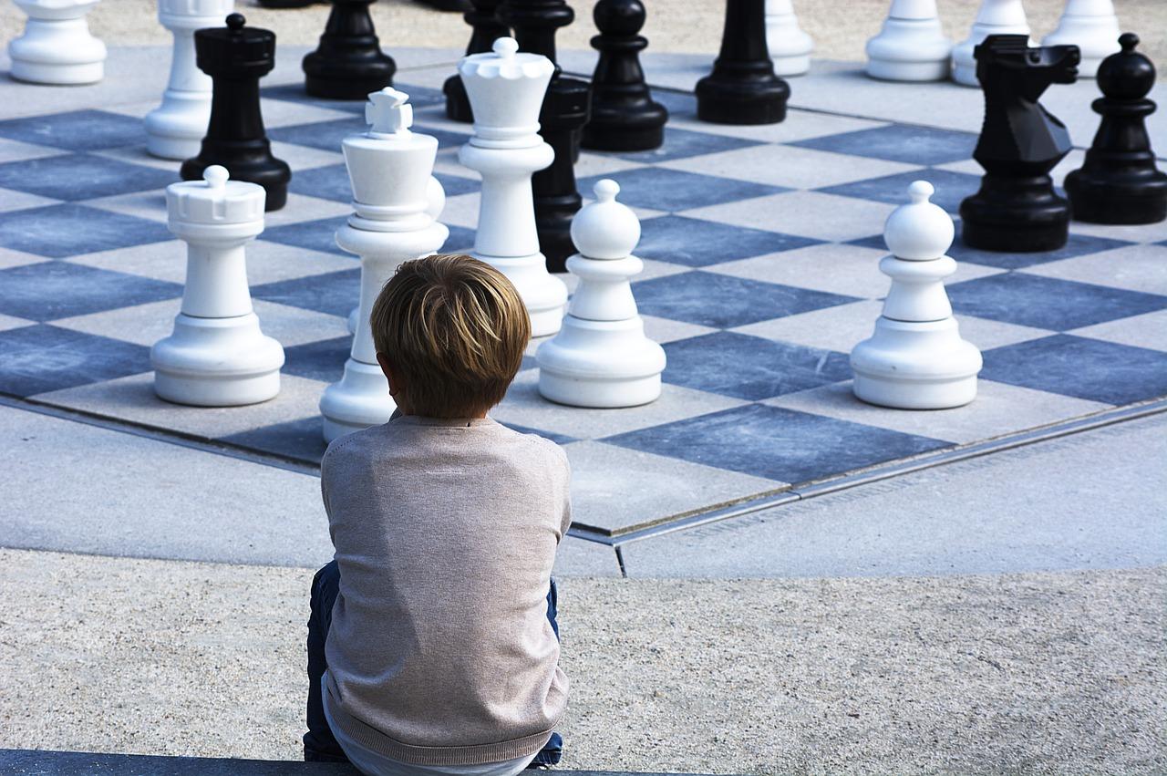 enfant regardant un géant jeu d'échecs par Positive_Images de Pixabay