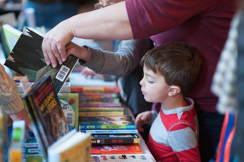 une maman choisit un livre avec ses enfants