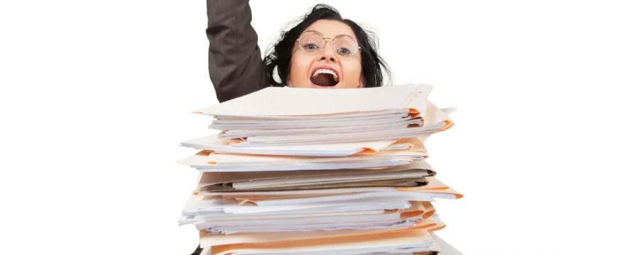 Woman behind stack of paperwork