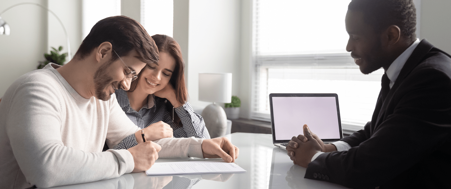 Man sitting across two clients signing papers