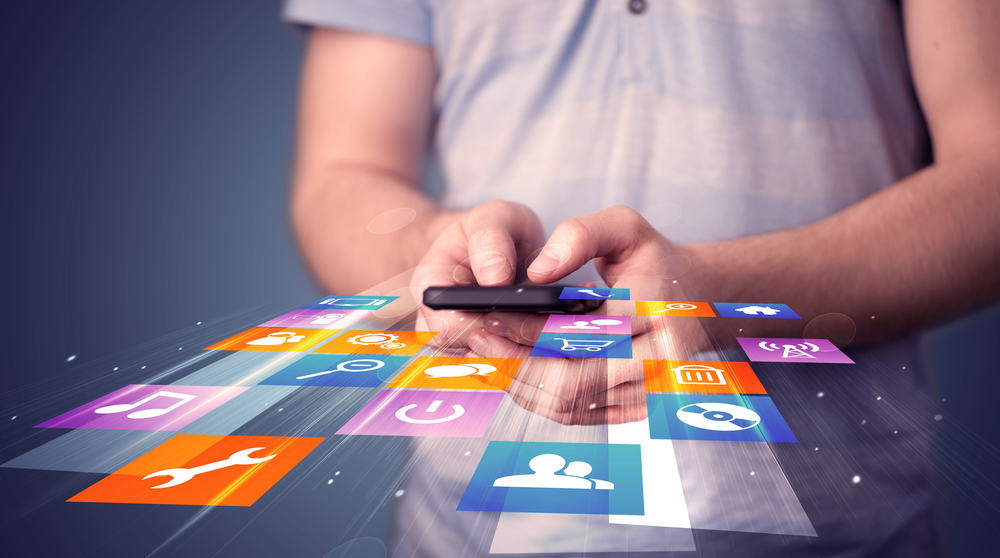 Man holding smartphone with colourful mobile app icons