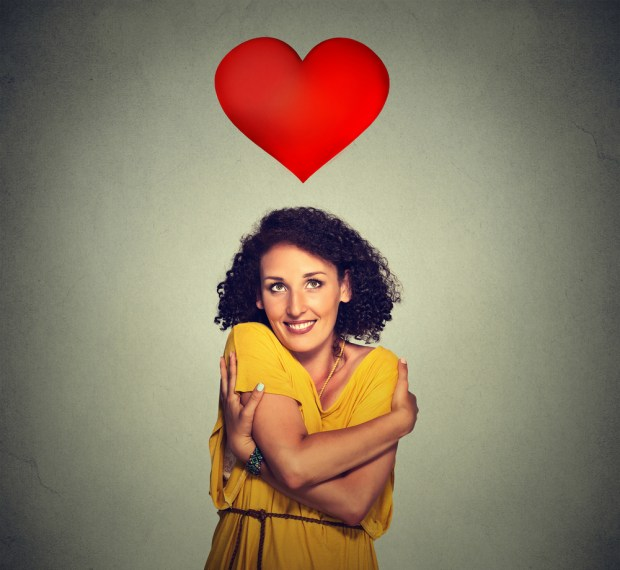 portrait smiling woman holding hugging herself with red heart ab