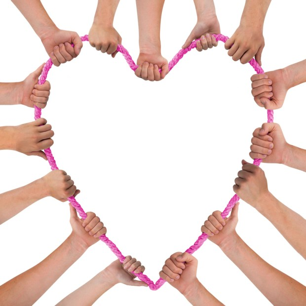 Hands holding pink heart isolated on white