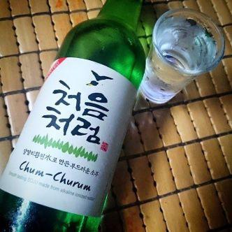 Botella de soju y al lado un chupito de soju fresco