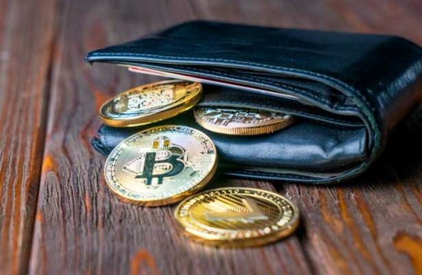 Black leather wallet with Bitcoin coins sticking out of it to illustrate a cryptocurrency wallet