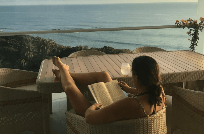 Woman reading peacefully by ocean