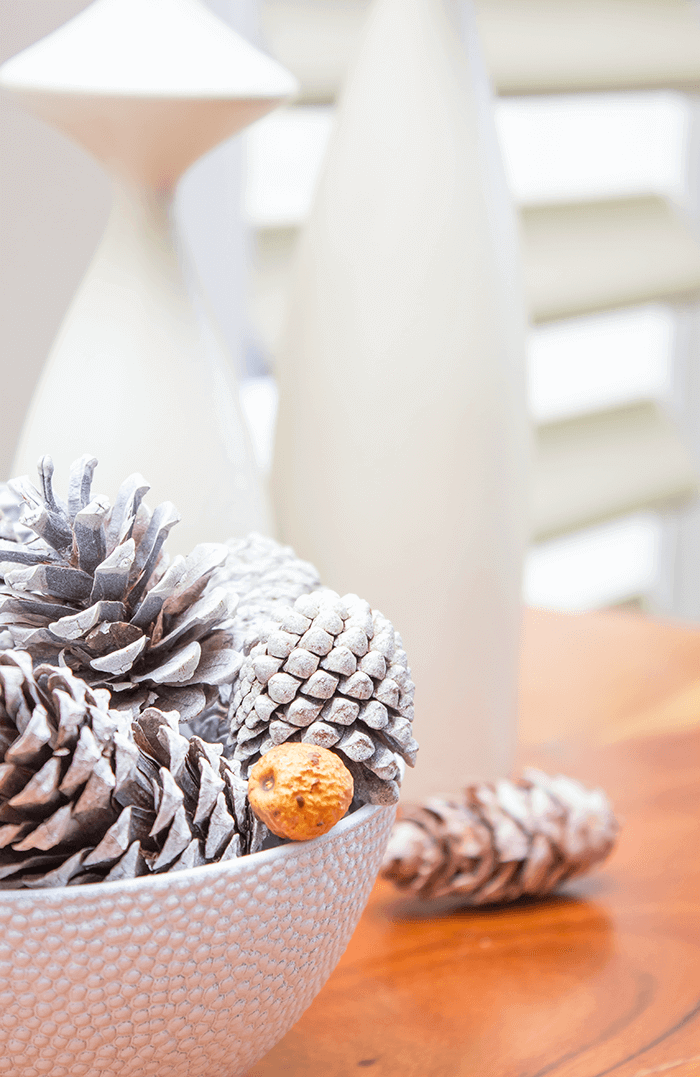 Finish of a fall vignette with this easy autumn decorating idea using a bowl, pinecones, and nuts.