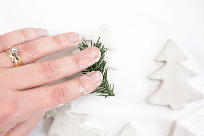 Gently press synthetic or real greenery into the Christmas tree clay ornaments.