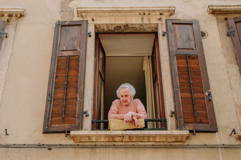 Old Lady Leaning from her balcony chatting to strangers in Trento, Italy