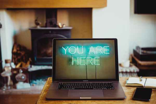 laptop with neon inscription on screen you are here