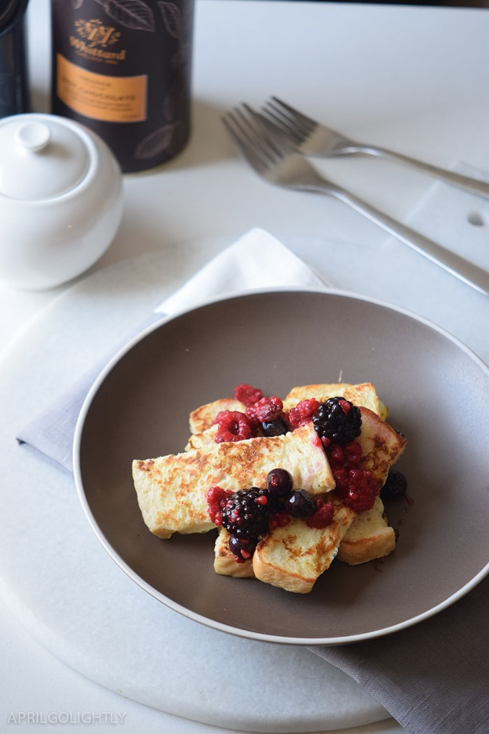 Easy French Toast Sticks recipe perfect for breakfast or brunch made with fresh fruit like raspberries, blueberries, and blackberries with maple syrup on top