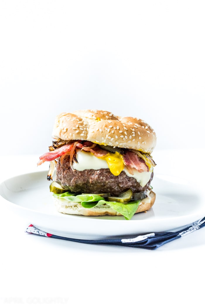 Classic Yellow Mustard Burger made with Beef Patties and French's Yellow Stoneground Mustard grilled and served with sautéed shallots, bacon, white american cheese, and diced pickles