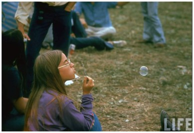 Jackie Barg sitting on the ground blowing bubbles during Woodstock (Jhon Dominis enLIFE)