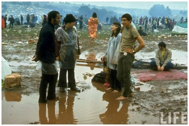 Young people standing in the mud water talking during Woodstock (Jhon Dominis en LIFE)