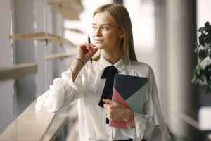 thoughtful worker with notebook and pen in office lobby