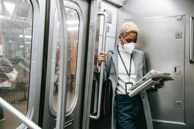 focused black woman in mask reading newspaper in metro train