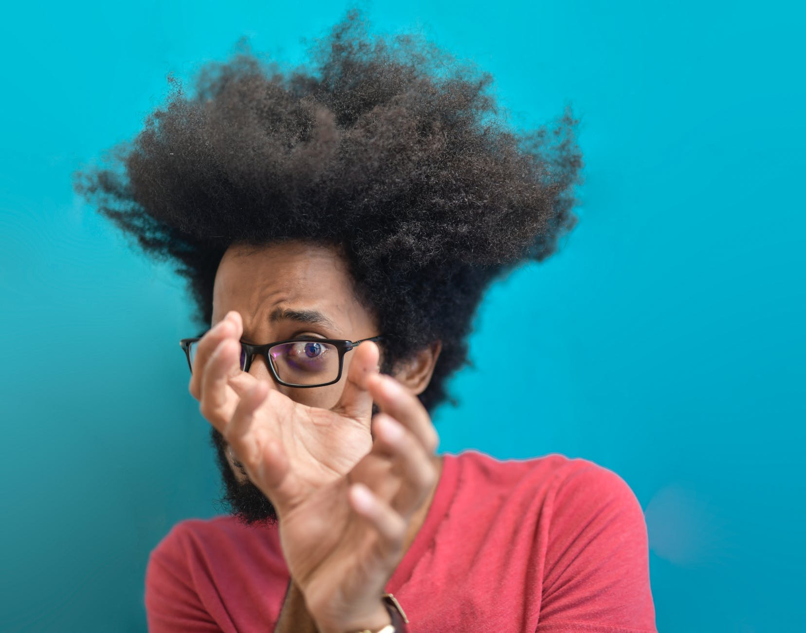 scared young ethnic man looking through hands on blue background in studio