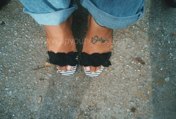 Black woman's feet in black and white stripe open toed sandal with black flower across the toes.