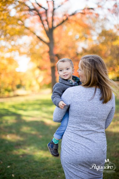 mom carries son by autumn leaves in prospect park